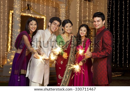 Portrait of friends holding sparklers - stock photo