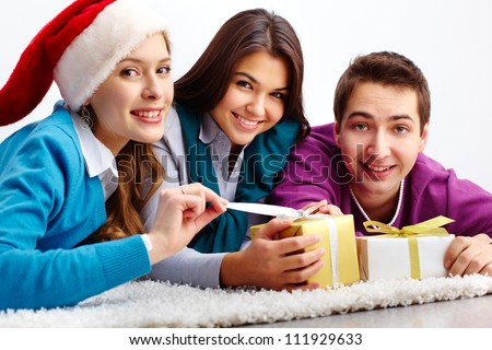 Portrait of friends lying on the floor and unwrapping small giftbox - stock photo