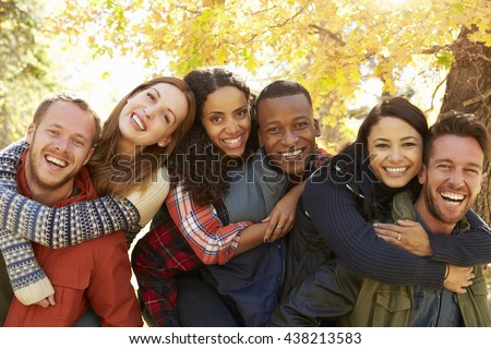 Portrait of friends piggybacking during a hike in a forest - stock photo