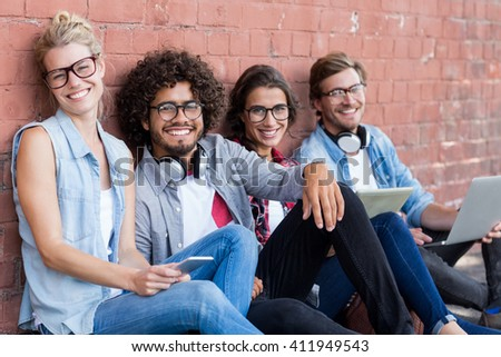 Portrait of friends sitting against wall using mobile phone, digital tablet and laptop - stock photo