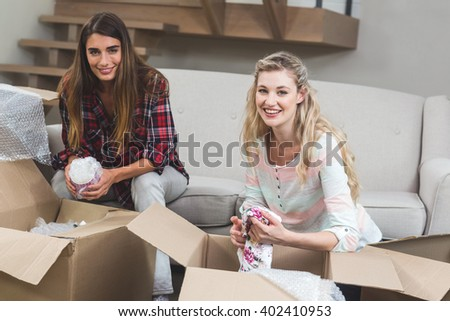 Portrait of friends unpacking carton boxes in their new house - stock photo