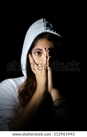 Portrait of frightened girl in hood on black background - stock photo