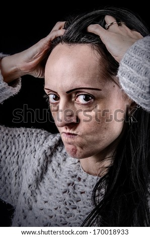 portrait of frustrated, angry woman on a black background  - stock photo