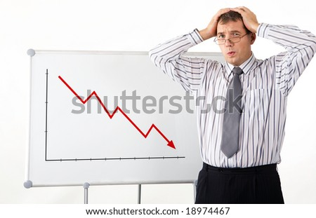 Portrait of frustrated man touching his head with whiteboard representing decreasing graph on it - stock photo