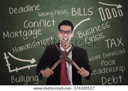 Portrait of frustrated young businessman cutting his neck with a clippers - stock photo