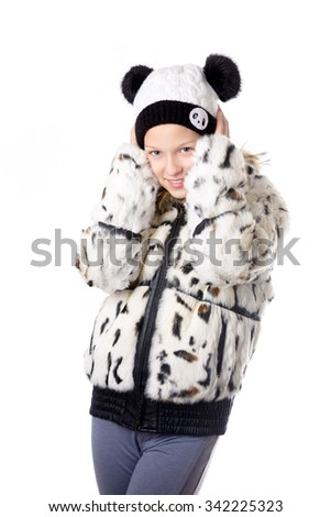 Portrait of funny beautiful casual caucasian teenage girl wearing white winter coat and knitted hat, shivering from cold, studio image, white background - stock photo