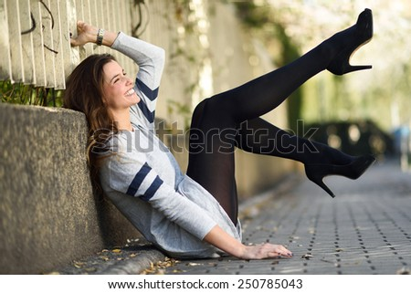 Portrait of funny female model of fashion with high heels sitting on the floor - stock photo