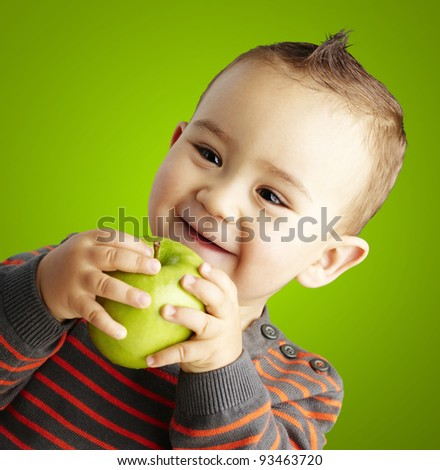 portrait of funny kid holding green apple and smiling over green background - stock photo