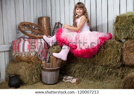 Portrait of funny little blond girl villager in rubber boots dressed luxuriant wavy ball dress with frill sitting on haystack  in wooden vintage hayloft - stock photo