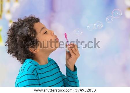 Portrait of funny little boy blowing soap bubbles   - stock photo