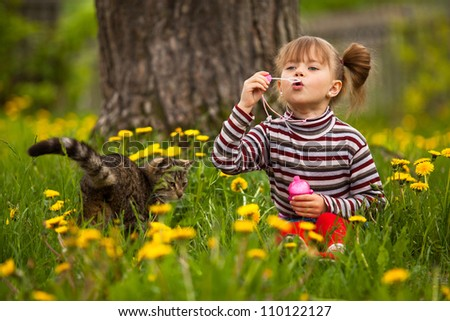 Portrait of funny lovely little girl and a cat, blowing soap bubbles. - stock photo