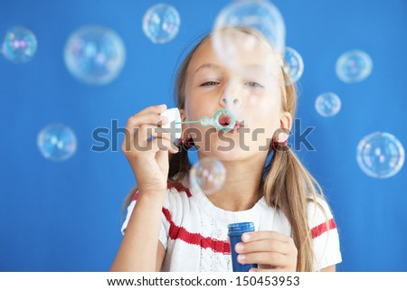Portrait of funny lovely little girl blowing soap bubbles - stock photo