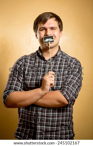 Portrait of funny man holding fake mustache on stick at mouth - stock photo