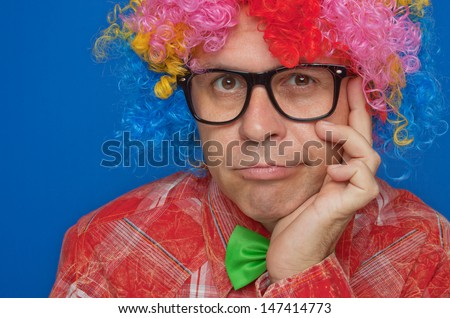 Portrait of funny smiling clown with party wig - stock photo