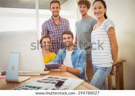 Portrait of gathered creative business team smiling at the camera - stock photo