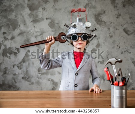 Portrait of geek child pretend to be businessman. Funny kid with toy virtual reality headset in modern loft office. Success, creative and innovation technology concept. Copy space for your text - stock photo