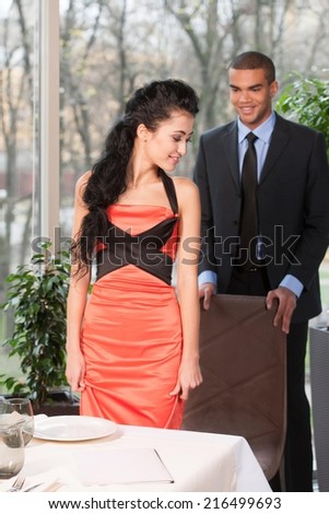 Portrait of gentleman helping his girlfriend at restaurant. Young man helping his girlfriend to accommodate on chair  - stock photo
