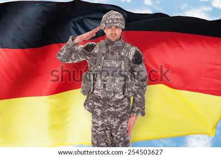 Portrait Of German Soldier Saluting In Front Of Flag - stock photo