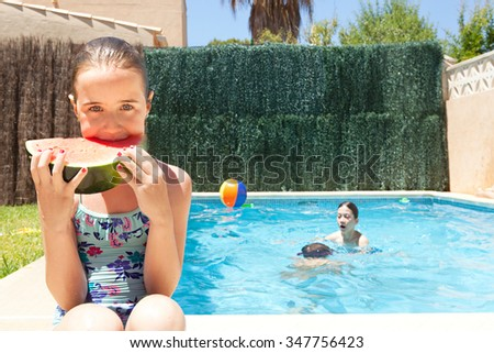 Portrait of girl child eating a slice of watermelon by a swimming pool with joyful friends having fun playing in a home garden on a sunny holiday, outdoors. Active kids lifestyle exterior vacation. - stock photo