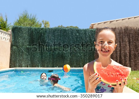 Portrait of girl child smiling eating a slice of watermelon by a swimming pool with joyful children playing in a home garden on a sunny holiday, outdoors. Active kids lifestyle exterior vacation. - stock photo