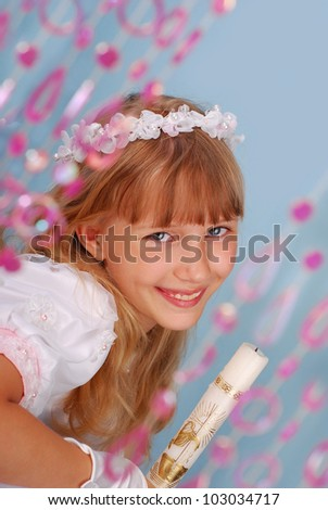 portrait of girl going to the first holy communion holding a candle and posing in studio - stock photo