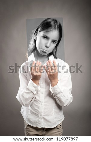 portrait of girl holding a photography of her with sad expression - stock photo