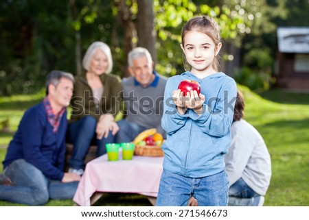 Portrait of girl holding apple while family in background at campsite - stock photo