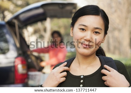 Portrait of girl in front of car on college campus - stock photo