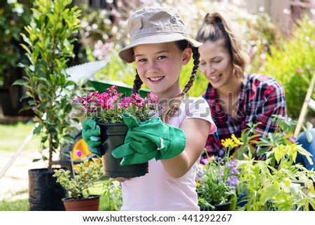 Portrait of girl standing in garden with flower pot while mother gardening in background - stock photo