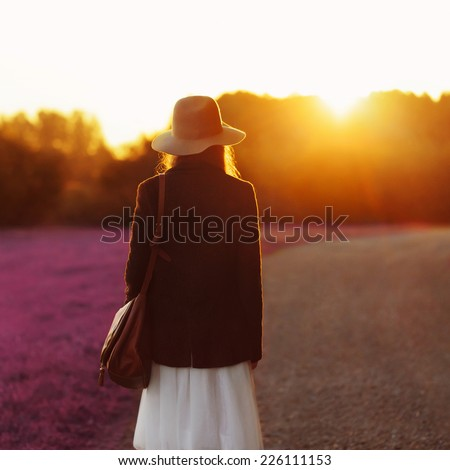 Portrait of girl walking down among the blooming fields into sunset light. Back to camera. Outside - stock photo