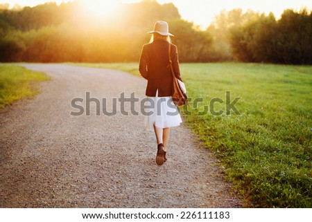 Portrait of girl walking down the road among fields in sunset light. Back to camera. Outside. - stock photo
