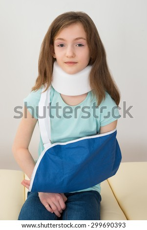 Portrait Of Girl Wearing Neck Brace And Arm Sling - stock photo