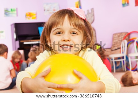 Portrait of girl with ball and friends on back - stock photo