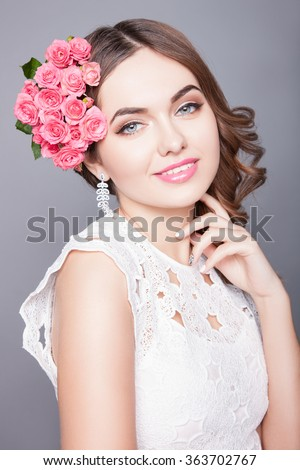 Portrait of girl with dark hair on a gray background, beautiful makeup on her face.Attractive girl with perfect skin.An attractive young woman with makeup on his face and flowers in her hair. - stock photo