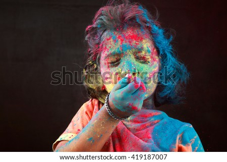 Portrait of girl with face smeared with colors blows colos in a dark background. Concept for Indian festival Holi. - stock photo