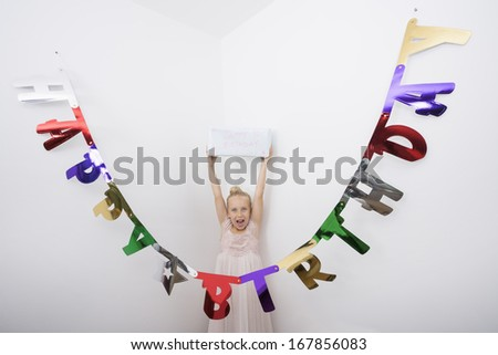 Portrait of girl with mouth open holding birthday gift over head - stock photo