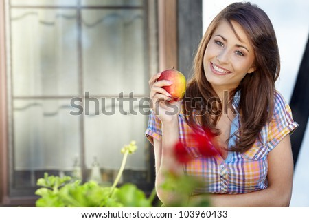 Portrait of girl with red apple against green garden. - stock photo