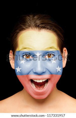 portrait of girl with venezuelan  flag painted on her face - stock photo