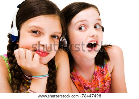 Portrait of girls listening to music on headphones isolated over white - stock photo