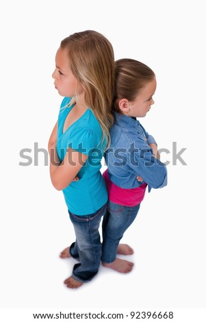 Portrait of girls standing back to back against a white background - stock photo