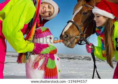 Portrait of girls with horse and snowman in winter landscape. - stock photo