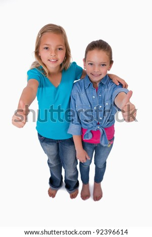 Portrait of girls with the thumbs up against a white background - stock photo