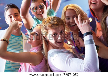 Portrait of glad guy and girl dancing at party with friends on background - stock photo
