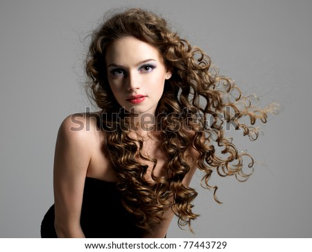 Portrait of glamour beautiful young woman with long curly hair - stock photo