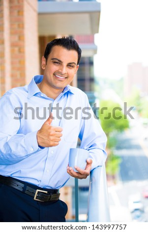Portrait of good looking businessman giving you a thumbs up, enjoying a drink, standing on his balcony - Isolated on a city background - stock photo