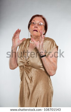 Portrait of good looking senior woman wearing glasses with expressive face showing emotions. Scared and frightened. Acting young. Studio shot isolated on grey background. - stock photo