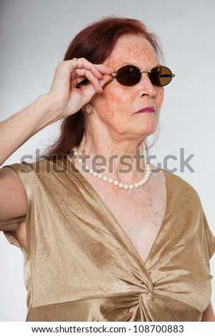 Portrait of good looking senior woman wearing sunglasses with expressive face showing emotions. Acting young. Studio shot isolated on grey background. - stock photo