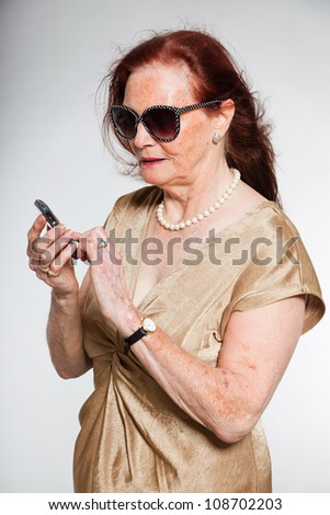 Portrait of good looking senior woman wearing sunglasses with expressive face showing emotions. Calling with cell phone. Acting young. Studio shot isolated on grey background. - stock photo