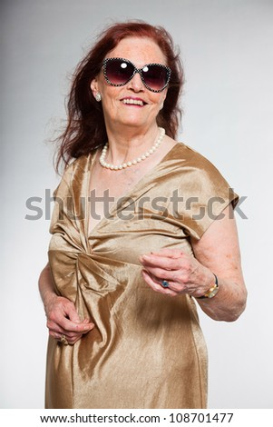 Portrait of good looking senior woman with expressive face showing emotions. Acting young. Studio shot isolated on grey background. - stock photo
