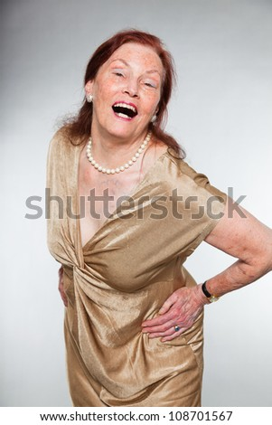 Portrait of good looking senior woman with expressive face showing emotions. Screaming. Acting young. Studio shot isolated on grey background. - stock photo